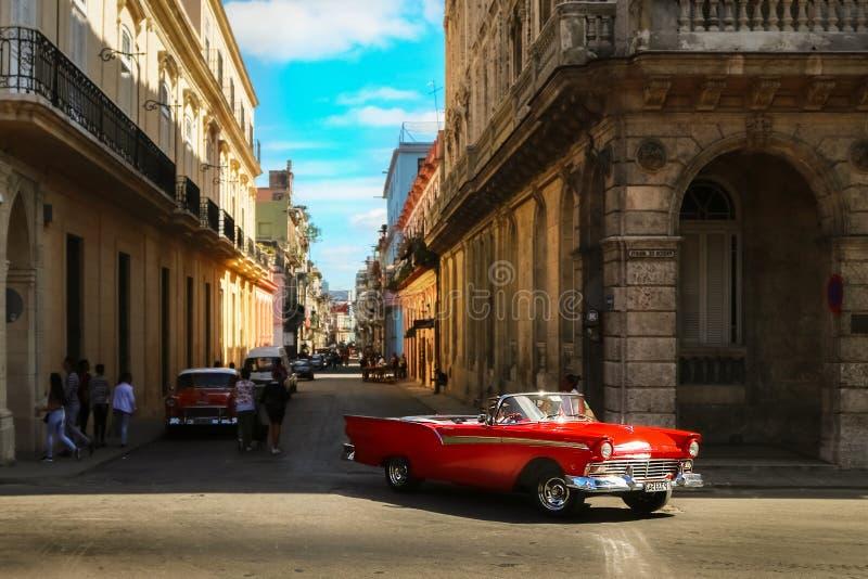 Cuba, Havana - Januari 16, 2019: Oude Amerikaanse rode auto in de oude stad van Havana tegen de achtergrond van Spaanse koloniale royalty-vrije stock afbeelding