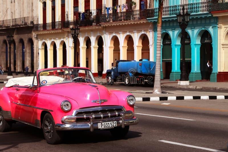 Cuba, Havana - Januari 16, 2019: Oude roze auto in de oude stad van Havana tegen de achtergrond van Spaanse koloniale architectuu stock afbeeldingen