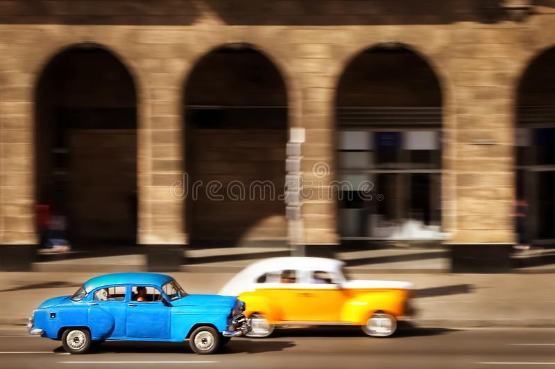 Cuba, Havana - January 16, 2019: Old yellow and blue cars in the old city of Havana against the backdrop of Spanish colonial archi stock images