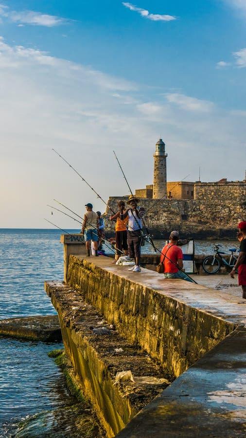 cuba havana Juni 2018 El Malecon av havannacigarren: kubanskt folk som fiskar på solnedgången royaltyfria bilder
