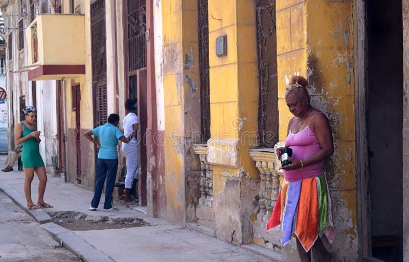 Cuba, Havana, o 10 de fevereiro de 2018: mulheres pobres que esperam fora de suas casas na rua fotos de stock
