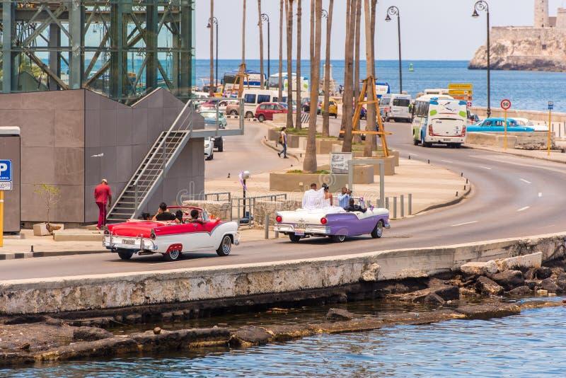 CUBA, LA HABANA - 5 DE MAYO DE 2017: Coches retros coloridos americanos que viajan a lo largo de la costa Copie el espacio para e fotos de archivo libres de regalías