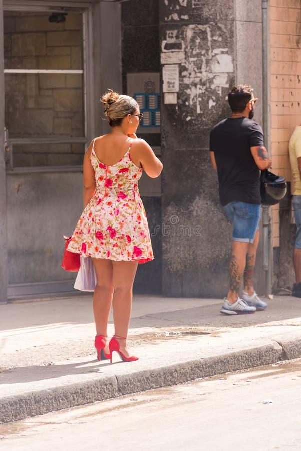 CUBA, LA HABANA - 5 DE MAYO DE 2017: Muchacha en un vestido en una calle de la ciudad Copie el espacio para el texto vertical foto de archivo libre de regalías