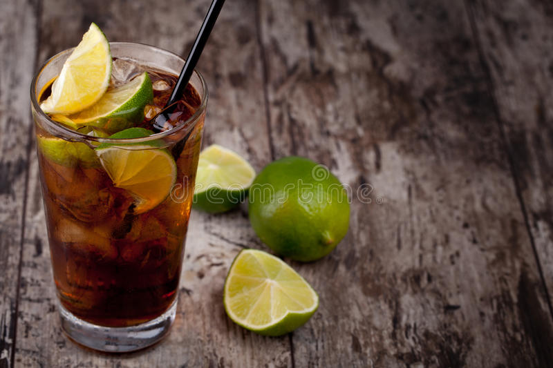Cuba Libre. Drink with lime on a wooden table stock photography