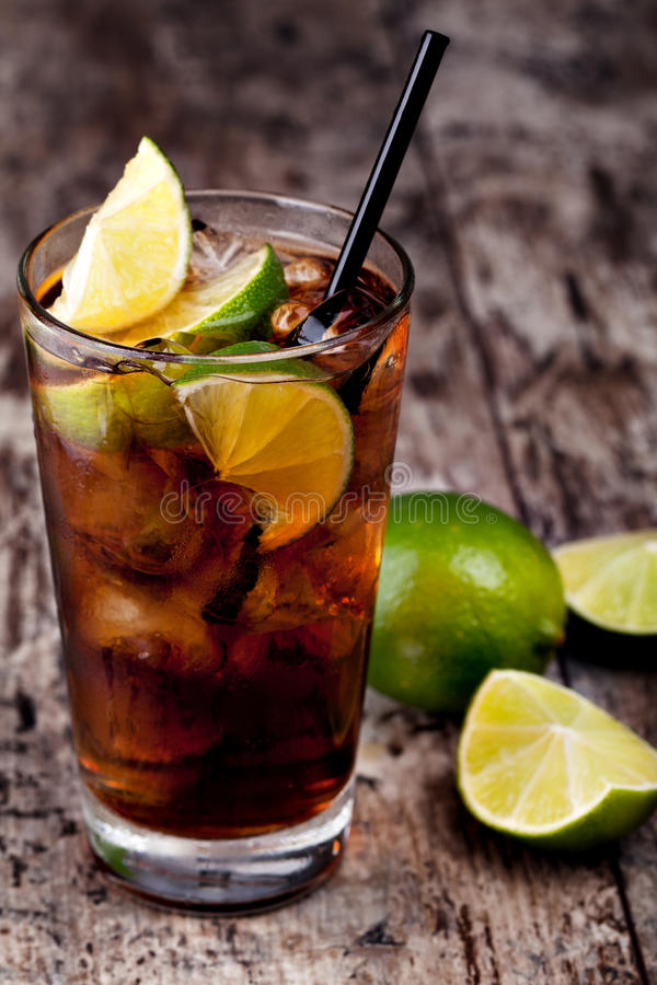 Cuba Libre. Drink with lime on a wooden table royalty free stock image