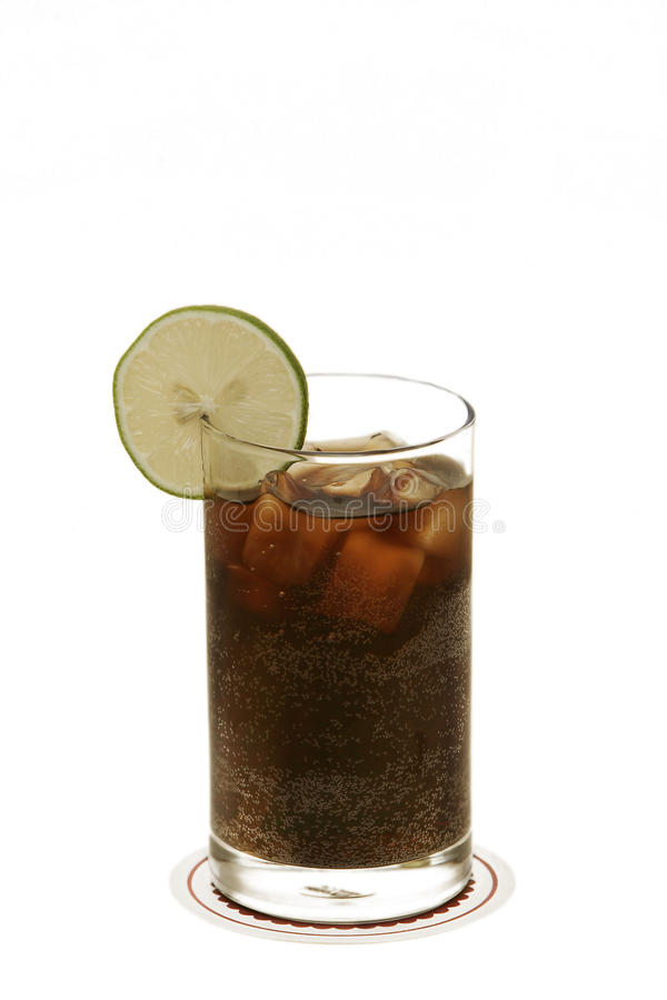 Cuba Libre Cocktail. Big glass filled with Cuba Libre cocktail, ice cubes and slice of lime isolated on white studio background royalty free stock image