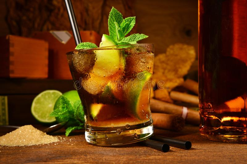 Cuba Libre Cocktail with Cigars. On wooden Background stock photography