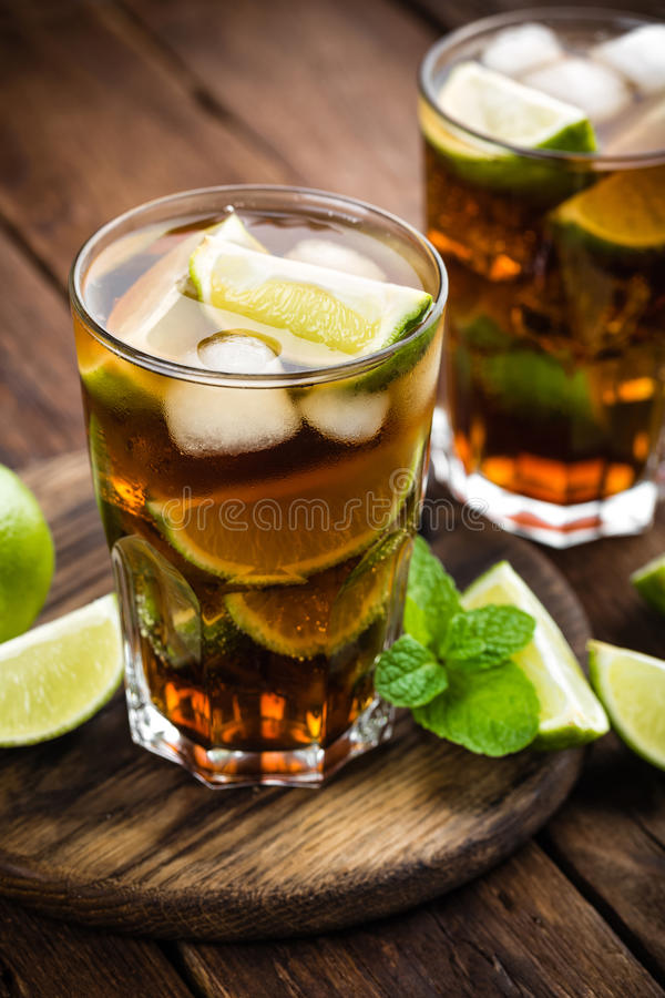 Cuba Libre cocktail with cola, lime and ice in glass, cold longdrink. On wooden background royalty free stock photo