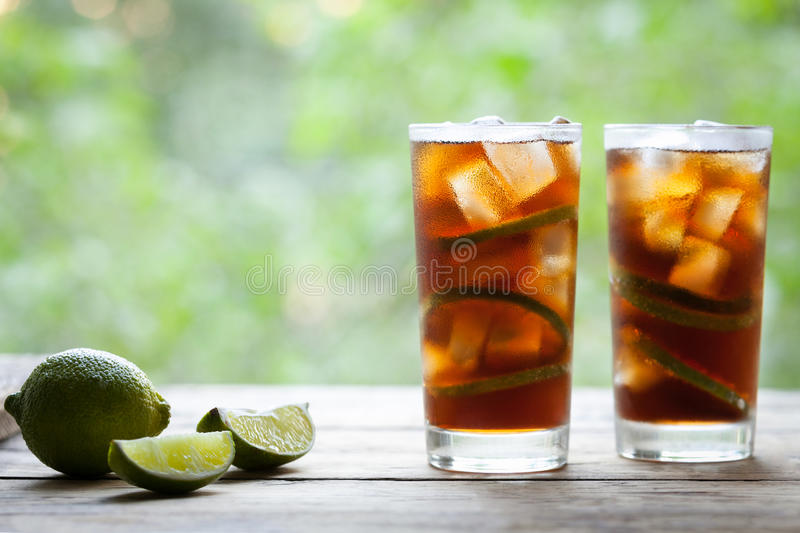 Cuba Libre cocktail with lime, ice, mint and rum on wooden table with a view to the terrace. Copy space for text. Close up summer beverage. Cold longdrink or stock photography