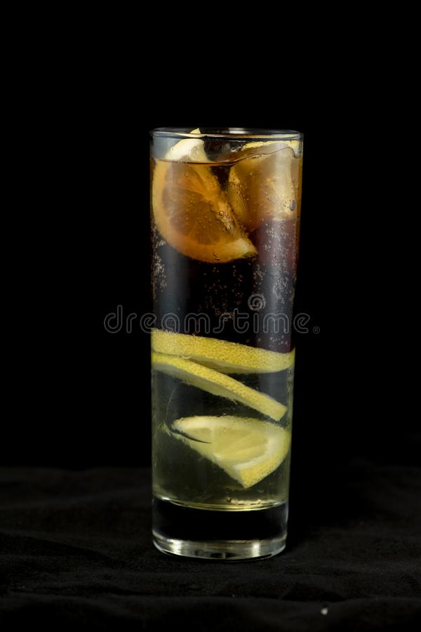 Cuba Libre cocktail with rum, coke and lime juice with lime wedge and full of ices stock photo