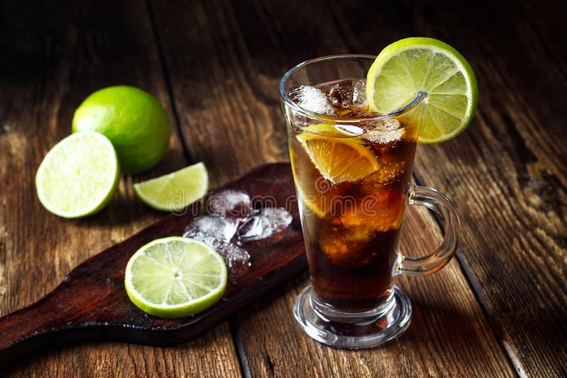 Cuba Libre coctail. With ice and lime on wooden table royalty free stock images