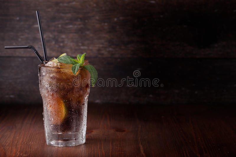 Cuba libre. Drink with lime on a wooden table royalty free stock photography