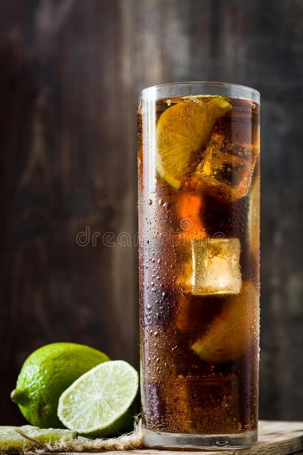 Cuba libre. Cocktail with rum, lime and ice on wooden table. royalty free stock images