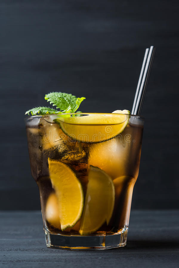 Cuba libre with lime. On black wooden table stock images