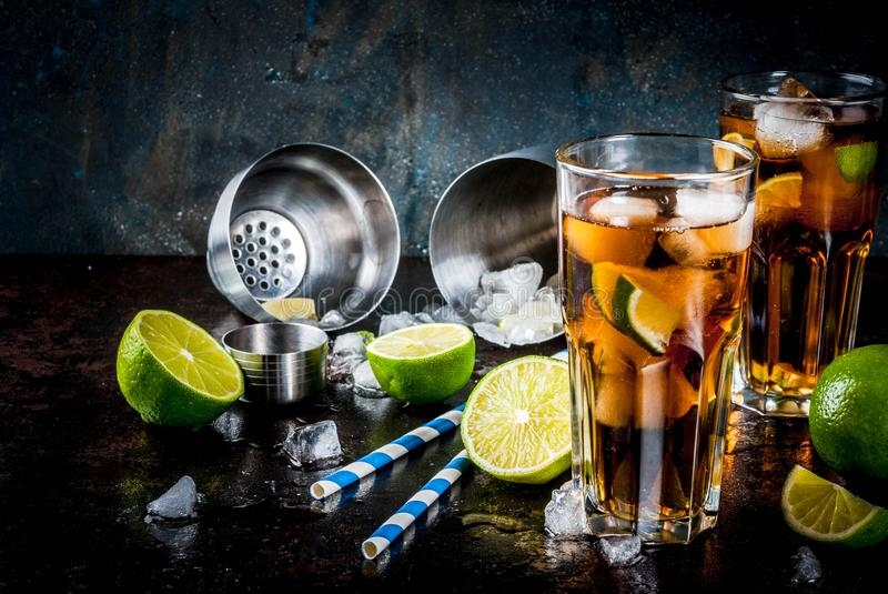 Cuba Libre, long island cocktail. Cuba Libre, long island or iced tea cocktail with strong alcohol, cola, lime and ice, two glass, dark background copy space stock photos