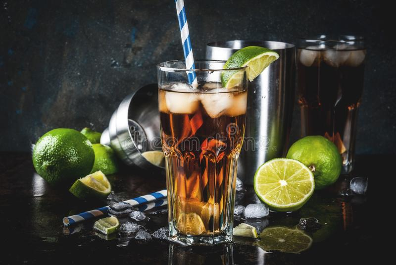Cuba Libre, long island cocktail. Cuba Libre, long island or iced tea cocktail with strong alcohol, cola, lime and ice, two glass, dark background copy space stock image