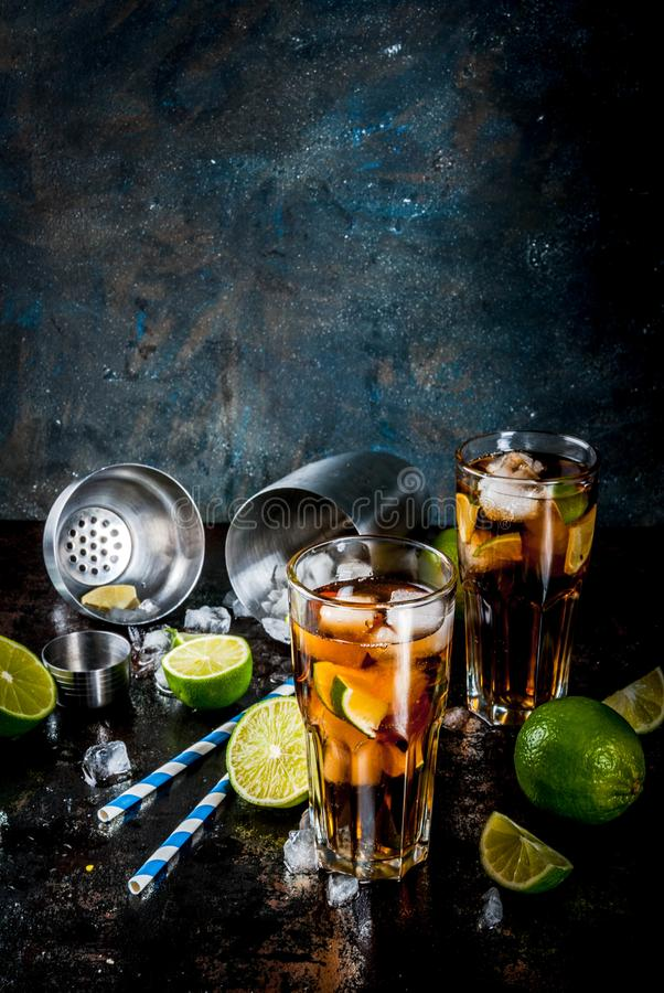 Cuba Libre, long island cocktail. Cuba Libre, long island or iced tea cocktail with strong alcohol, cola, lime and ice, two glass, dark background copy space stock photo