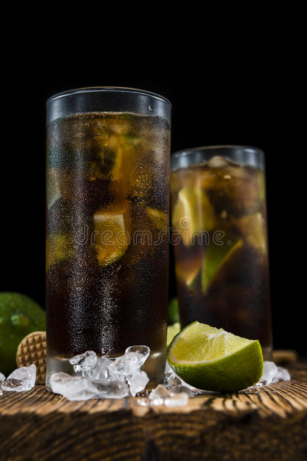 Cuba Libre. Longdrink with pieces of fresh lime and crushed ice on wooden background royalty free stock images