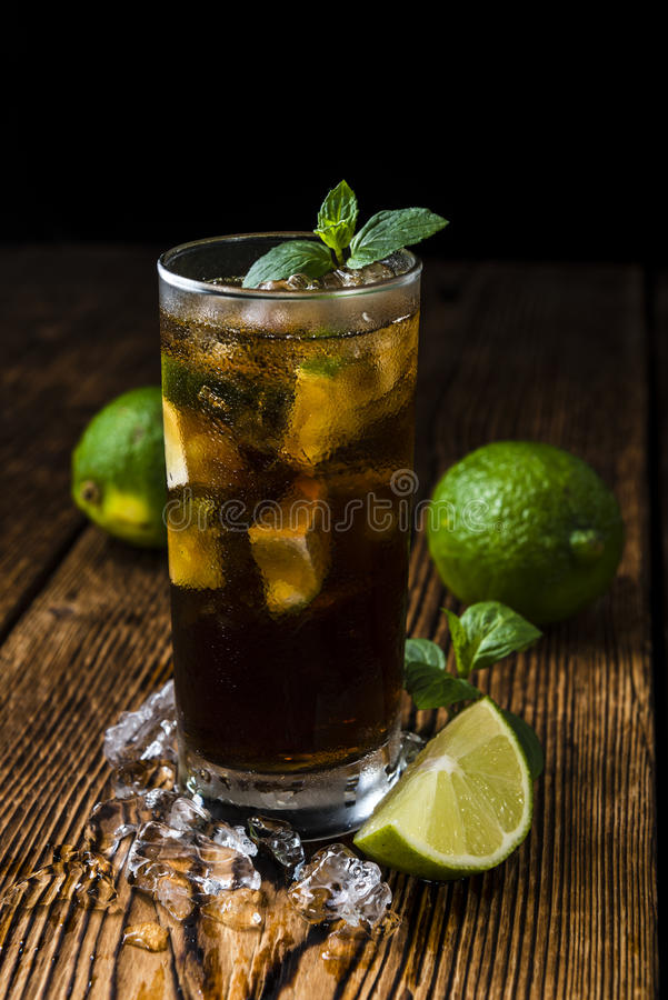 Cuba Libre. Longdrink with pieces of fresh lime and crushed ice on wooden background royalty free stock photography
