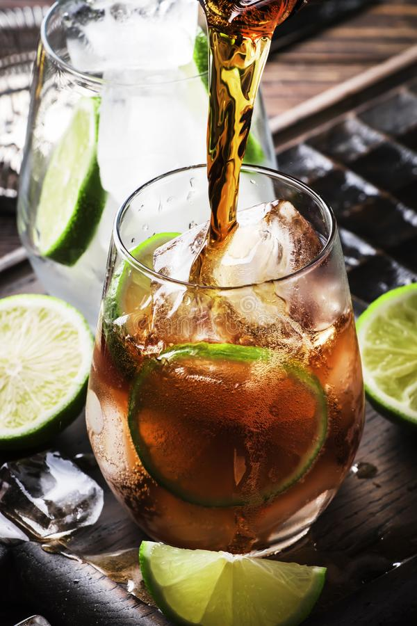 Cuba libre preparation alcohol cocktail with golden rum, lemon juice, cola, lime and ice, dark bar counter background, bar tools, stock photo