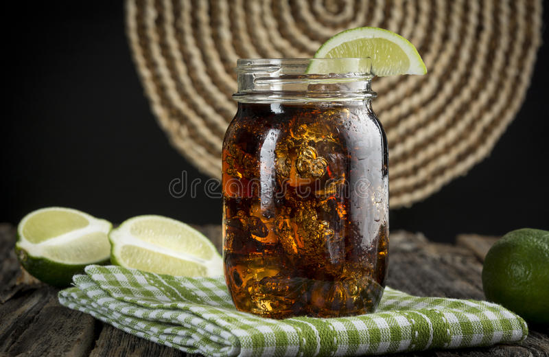 Cuba Libre!. Cuba Libre or rum and cola drink with ice and lime in mason jar royalty free stock images