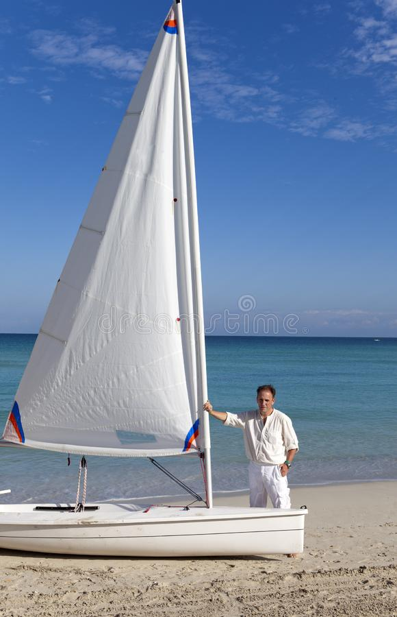 Cuba. A man on the blue sea next to a boat with a sail stock photography