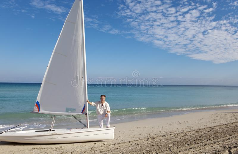 Cuba. A man on the blue sea next to a boat with a sail stock images