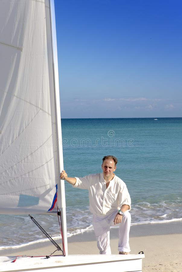 Cuba. A man on the blue sea next to a boat with a sail stock photos