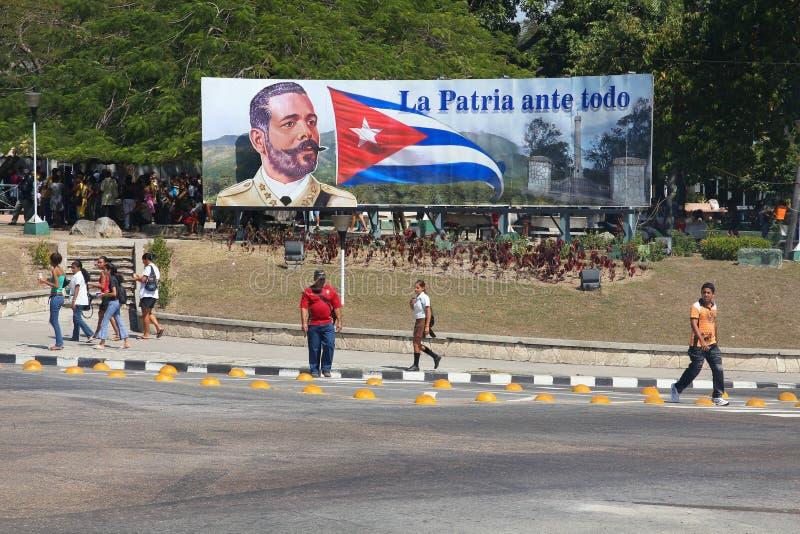 Cuba political sign. SANTIAGO, CUBA - FEBRUARY 10, 2011: People walk by patriotic propaganda sign in Santiago de Cuba. Cuban revolution of 1953-1959 increased stock photos