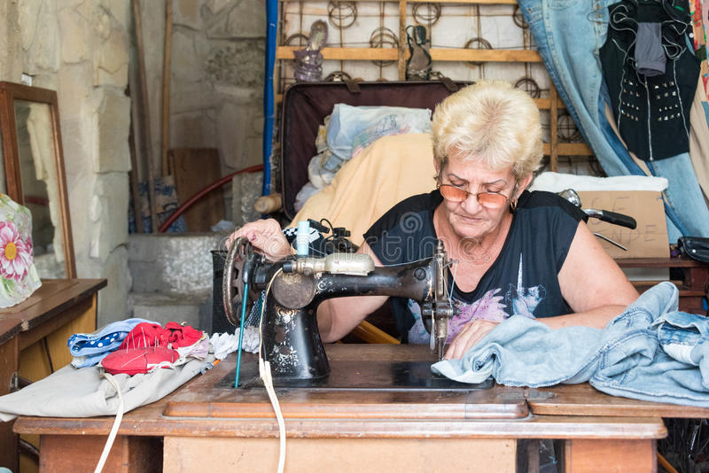 Cuba self employment: seamstress working in her house-Cuba. Cuban self employed seamstress woman sewing old clothing or creating new ones in her home in order to stock photos