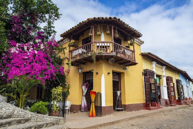 Cuba Trinidad Hoek van oud twee vloer de bouwrestaurant met violette en purpere bloemen Mooie hemel met wolken royalty-vrije stock afbeeldingen