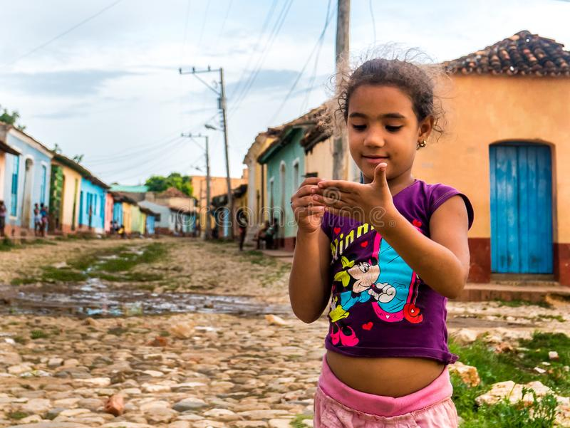 CUBA, TRINIDAD. June 2016: kid girl playing with pencil on the street, surrounded by colored houses of Trinidad. royalty free stock photo
