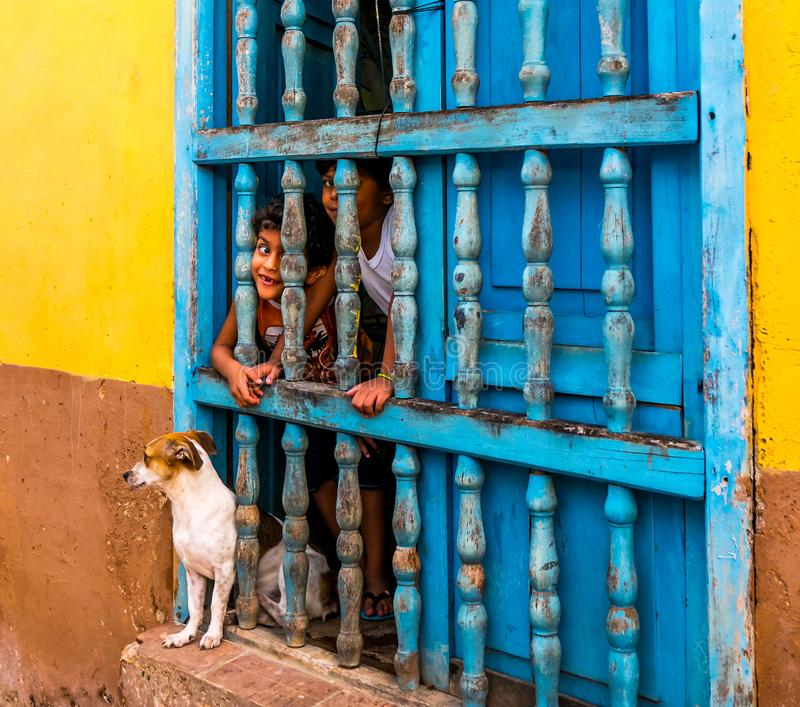 CUBA, TRINIDAD. June 2016: Two children looking out of the window of their house in Trinidad, also a dog is at the window. royalty free stock photos
