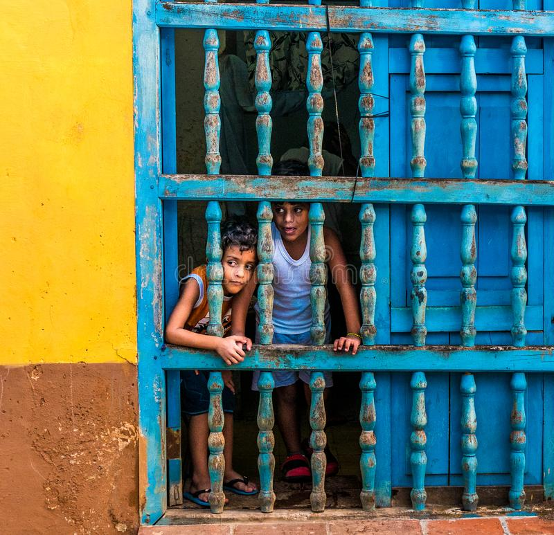 CUBA, TRINIDAD. June 2016: Two children looking out of the window of their house in Trinidad. stock photos