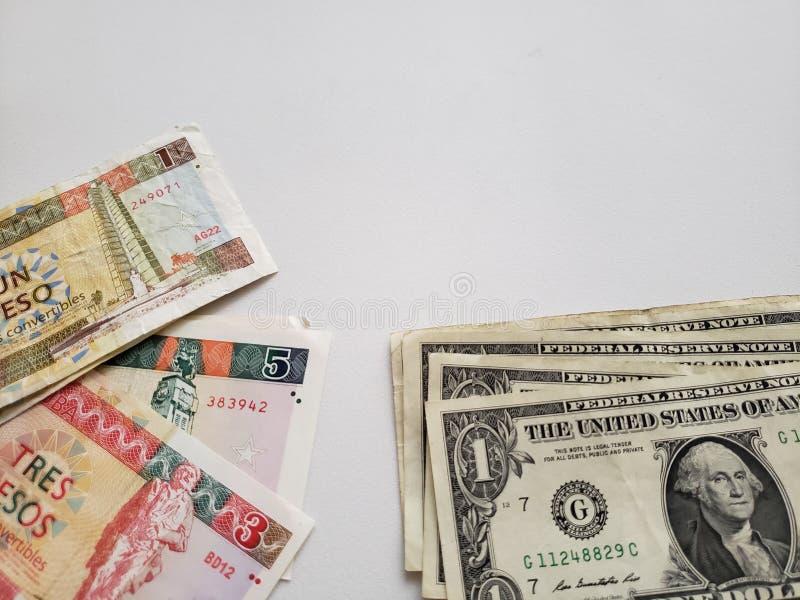 Cubaanse bankbiljetten van verschillende benamingen en Amerikaanse dollarrekeningen op witte achtergrond royalty-vrije stock foto
