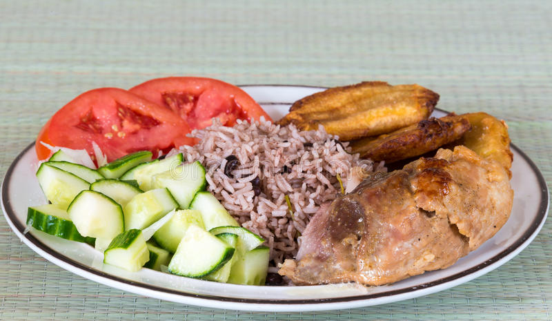 Cuban Cuisine: Traditional Creole Meal. Traditional Cuban cuisine: congri rice,fried green banana or chatinos, pork meat and vegetables on the plate on a gray stock photos