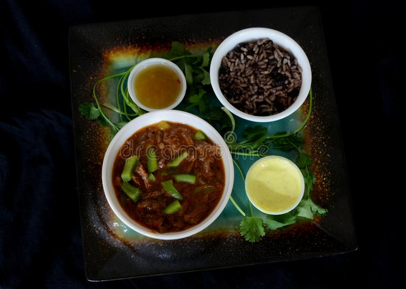Cuban Food In dark food mode. Traditional cuban plate ropa vieja with congri and sauces in dark food mode royalty free stock images