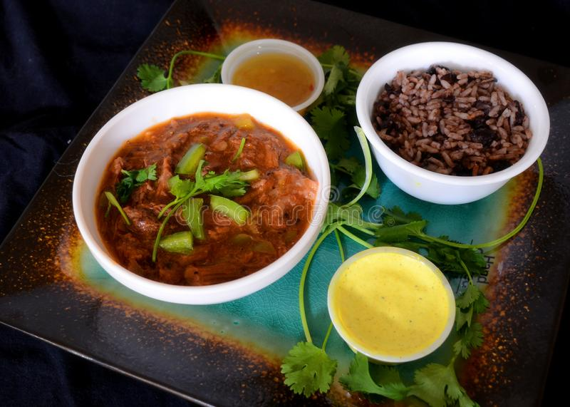 Cuban Food In dark food mode. Traditional cuban plate ropa vieja with congri and sauces in dark food mode royalty free stock photos