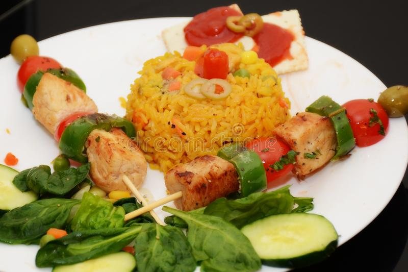 Cuban Food with Brillants Colors. Cuban Foods, Yellow Rice, Meat, Jalapenos and Tomatoes Cherry. Beautiful Food presentation stock images