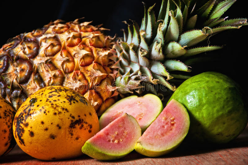 Cuban fruits, mango, guava and pineapple. Assortment of cuban fruits, mango, guava and pinneaple against black background royalty free stock images