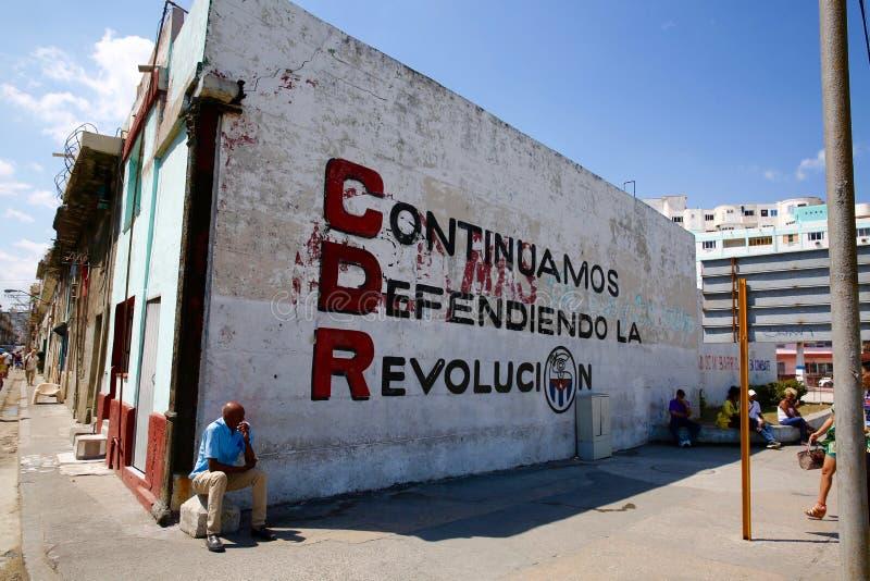 Cuban Government Propaganda Sign, Havana. A man rests in front of government propaganda urging citizens to continue to defend Cuba`s revolution royalty free stock image