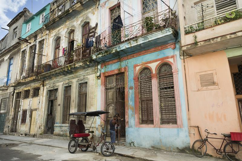 Cuban man holding unto old gate next to his vintage tricycle royalty free stock images