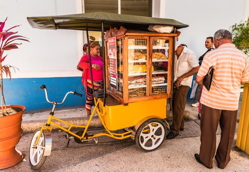 Cuban Pastry Vendor. Sancti Spiritus , Cuba / March 15, 2017: Pastry - Dulces - seller sells wares from a mobile stand powered by a three wheel bicycle stock photo