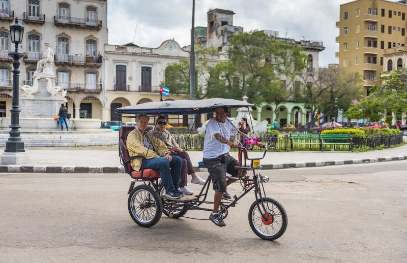 Cuban Pedicab In Old Havana. Havana, Cuba / March 22, 2016: Tourists explore Old Havana aboard a bicycle rickshaw stock photo