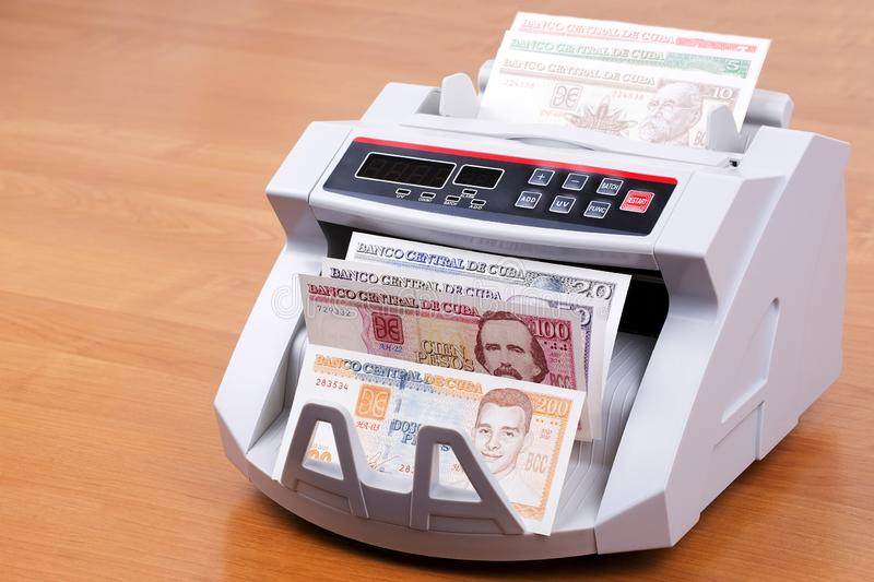 Cuban pesos in a counting machine royalty free stock images