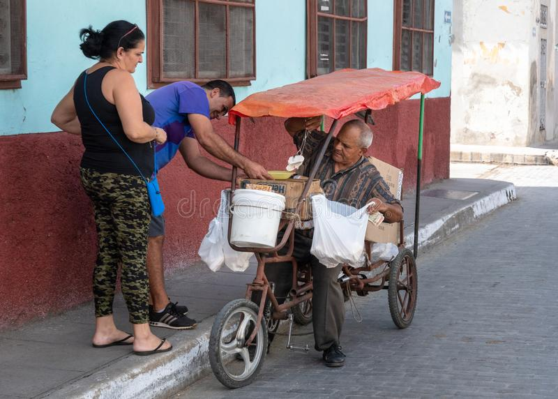 Santa Clara, Villa Clara, Cuba, 2019. Cuban senior man selling sweet food items in the streets. He uses a tricycle which is a popular mode of transport for self stock images