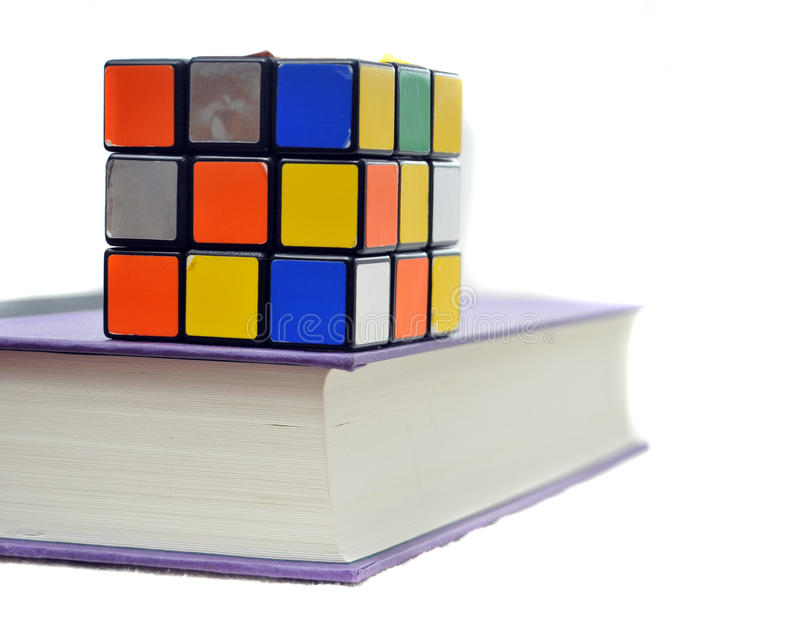 Cube on Book. Puzzle cube on top of thick book isolated on white background. You must contact Seven Towns Ltd for permission prior to any use of any of Rubik's stock photos