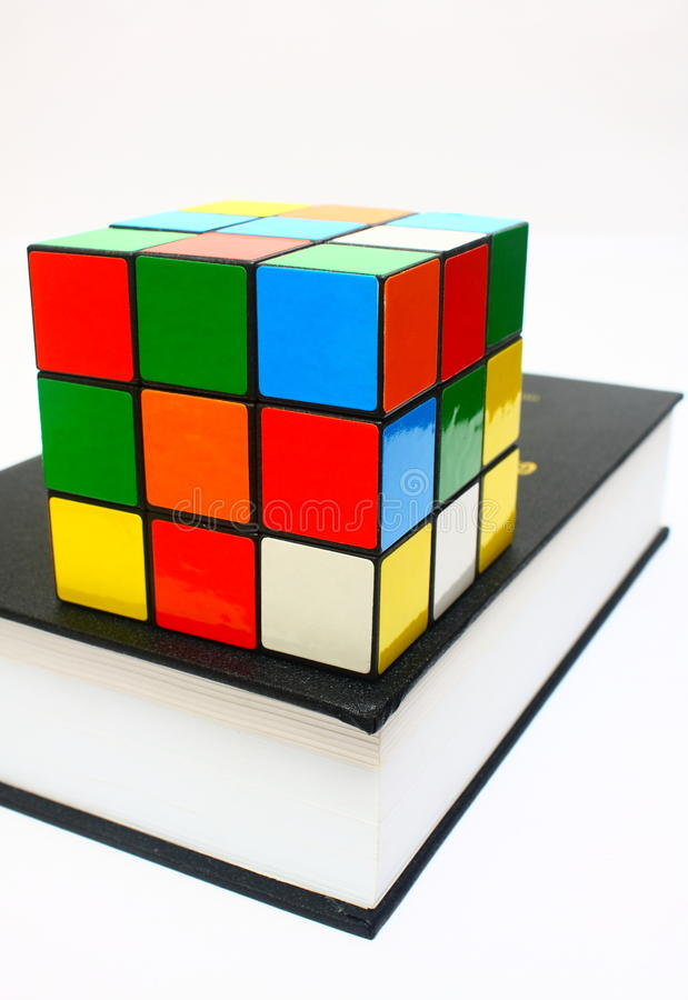 Cube on Book. Puzzle cube on top of thick book isolated on white background stock image