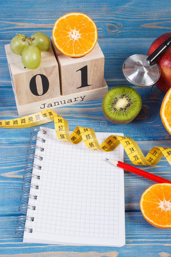 Cube calendar, fruits, dumbbells and tape measure, new years resolutions royalty free stock image