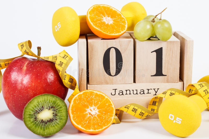 Cube calendar, fruits, dumbbells and tape measure, new years resolutions. January 1 on cube calendar, fresh fruits, dumbbells and tape measure, new years stock images